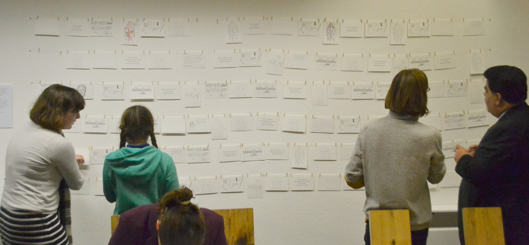 People placing postcards on the wall